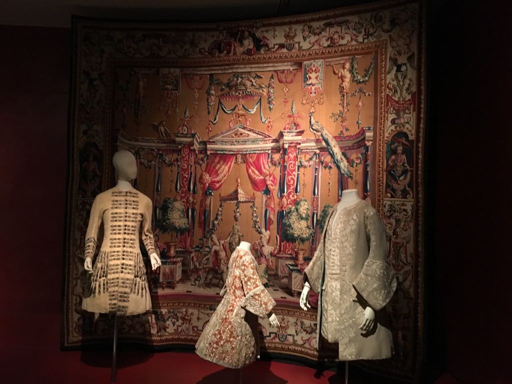 Offrande a Pan, tapestry from Beauvais, 17 th century is the background for a hunting jacket of embroidered leather1690, and justaucorps for child and adult