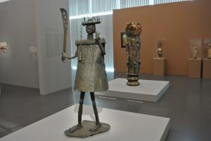 Benin sculpture by Akati Ekplétendo, dedicated to Gou, before 1858 and (behind) a 19 th century drum from the Ivory COsat