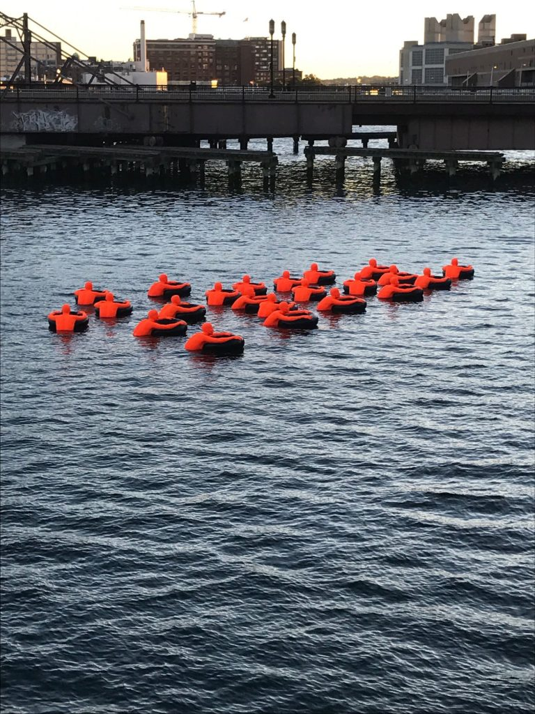 Ann Hirsch and Jeremy Angier, orange foam swimmers, are floating in the Fort Point Channel, near South Station, in Boston. Photo Brigid Williams